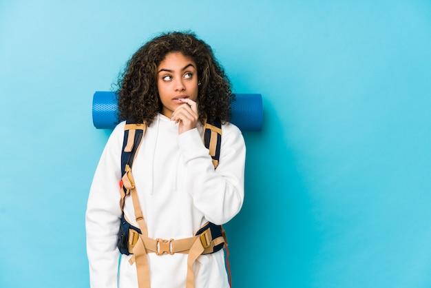 La giovane donna afroamericana di viaggiatore con zaino e sacco a pelo si è distesa pensando a qualcosa che esamina uno spazio della copia.