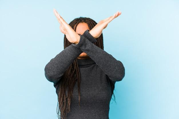 La giovane donna afroamericana isolata sulla parete blu che tiene due armi ha attraversato, concetto di rifiuto.