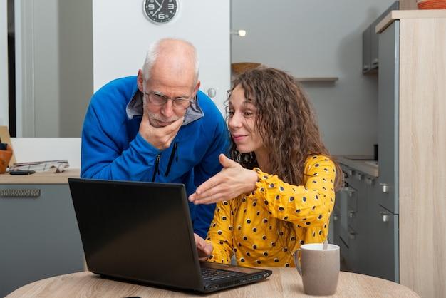La giovane donna aiuta l'anziano sul computer portatile