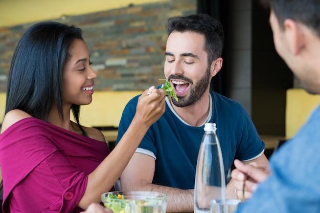La giovane donna alimenta l'insalata all'uomo