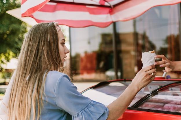 La giovane donna alla moda compra il gelato