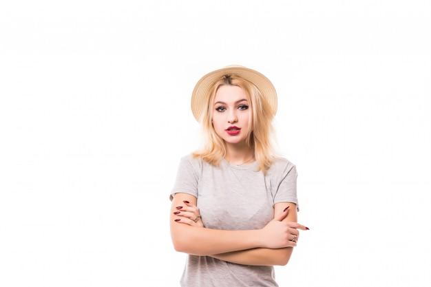 La giovane donna alla moda in cappello che sta con le armi ha piegato isolato sulla parete bianca