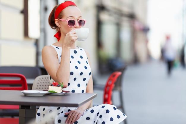 La giovane donna alla moda in un caffè della via beve il caffè. piacevole soggiorno in una giornata estiva.