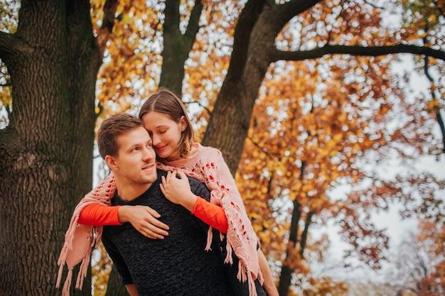 La giovane donna allegra e positiva si siede sulla schiena del ragazzo e si appoggia a lui