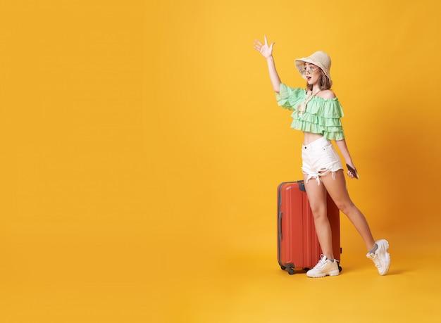 La giovane donna allegra si è vestita in vestiti dell'estate che stanno con una valigia