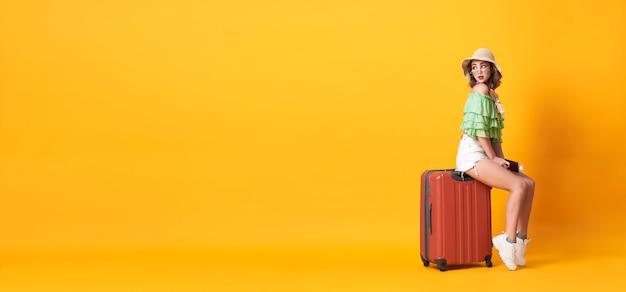 La giovane donna allegra si è vestita in vestiti dell'estate che tengono il passaporto