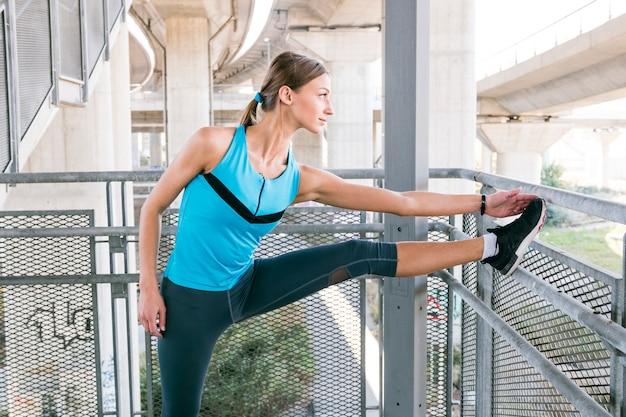 La giovane donna allegra sta allungando prima di fare jogging