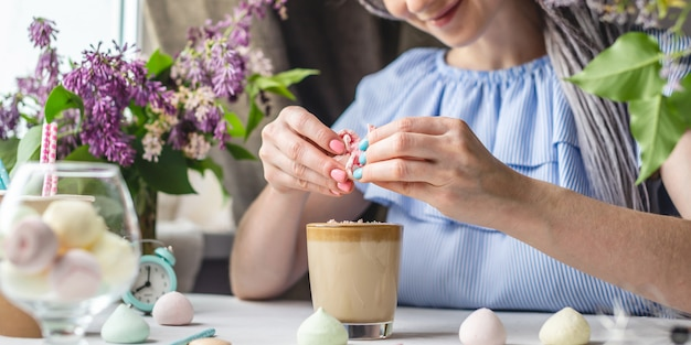 La giovane donna allegra sta rompendo la meringa e spruzza il delizioso caffè montato sulla cima