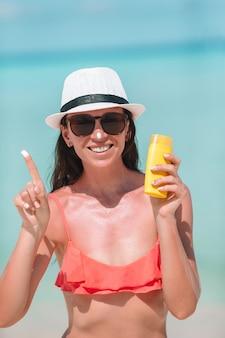 La giovane donna applica la crema sul suo naso alla spiaggia