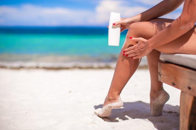 La giovane donna applica la crema sulle sue gambe abbronzate lisce al beac tropicale