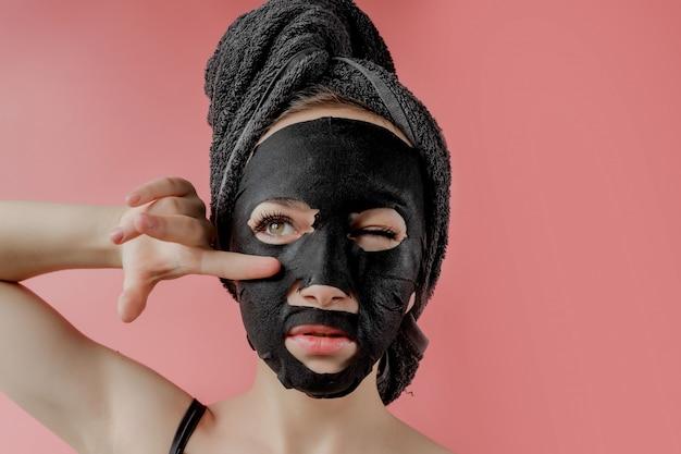 La giovane donna applica la maschera facciale nera del tessuto cosmetico sulla parete rosa. maschera peeling viso con carbone, trattamenti di bellezza spa, cura della pelle, cosmetologia. avvicinamento