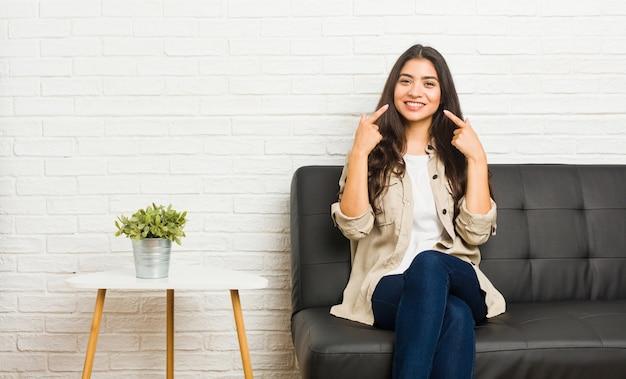 La giovane donna araba che si siede sul sofà sorride, indicando le dita alla bocca.