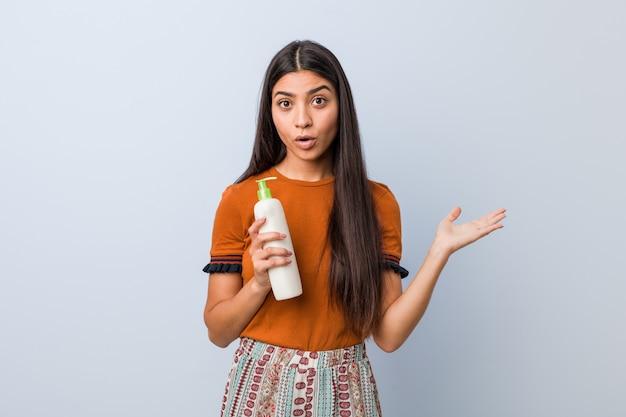 La giovane donna araba che tiene una bottiglia crema ha impressionato lo spazio della copia della tenuta sulla palma.