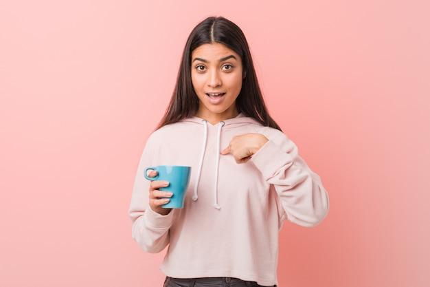 La giovane donna araba che tiene una tazza sorpreso indicando se stesso, sorridendo ampiamente.