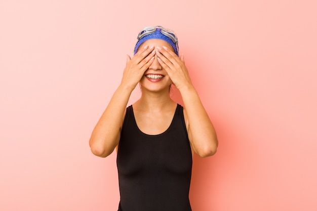 La giovane donna araba del nuotatore isolata copre gli occhi di mani, sorride ampiamente aspettando una sorpresa.