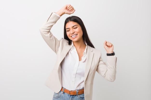 La giovane donna araba di affari contro una parete bianca che celebra un giorno speciale, salta e alza le braccia con energia.