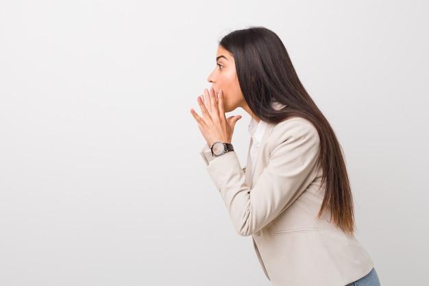 La giovane donna araba di affari isolata contro un bianco grida forte, tiene gli occhi aperti e le mani tese.