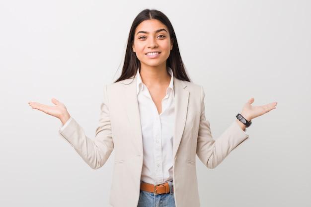 La giovane donna araba di affari isolata contro una parete bianca fa la scala con le armi, si sente felice e sicura.