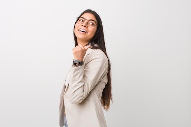 La giovane donna araba di affari isolata contro una parete bianca indica con il dito del pollice assente, ridente e spensierata.