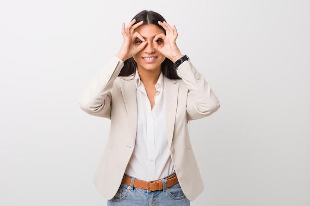 La giovane donna araba di affari isolata contro una priorità bassa bianca che mostra bene firma sopra gli occhi