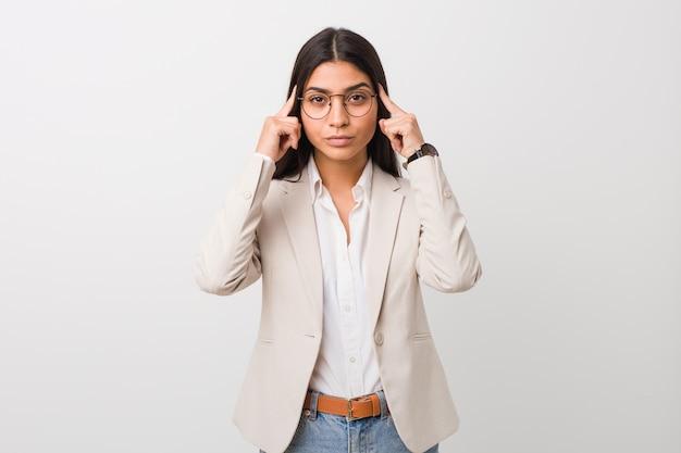 La giovane donna araba di affari isolata contro una priorità bassa bianca ha messo a fuoco su un'operazione, tenendo gli indici che indicano la testa.