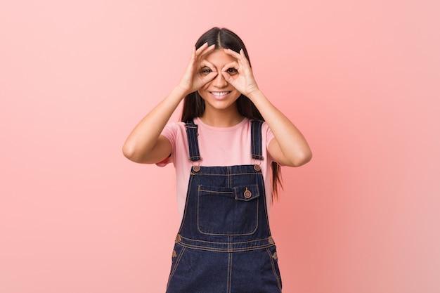 La giovane donna araba graziosa che indossa un dungaree dei jeans che mostra okay cede firmando un documento gli occhi