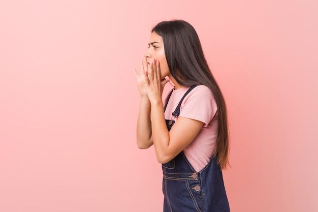La giovane donna araba graziosa che indossa una salopette di jeans grida forte, mantiene gli occhi aperti e le mani tese.