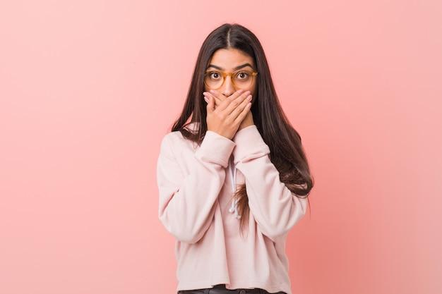 La giovane donna araba graziosa che indossa uno sguardo di sport casuale ha colpito la bocca coprente con le mani.