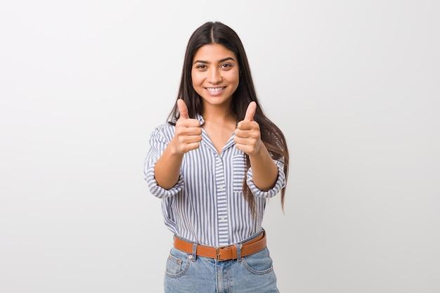 La giovane donna araba graziosa con i pollici aumenta, incoraggia qualcosa, sostiene e rispetta il concetto.
