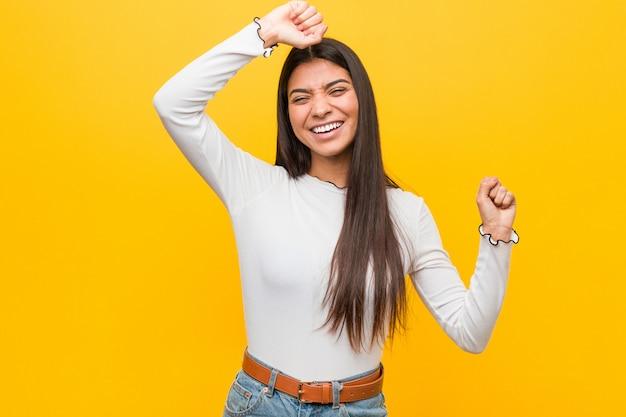 La giovane donna araba graziosa contro una parete gialla che celebra un giorno speciale, salta e alza le braccia con energia.