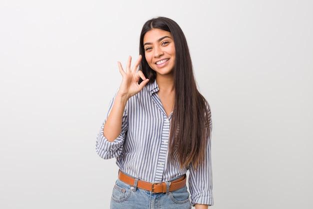 La giovane donna araba graziosa fa l'occhiolino e tiene un gesto giusto con la mano.