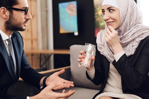 La giovane donna araba nel hijab prende la pillola.
