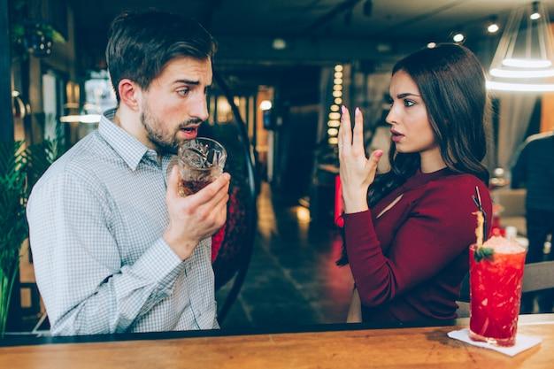 La giovane donna arrabbiata mostra la sua mano con l'anello su per l'uomo