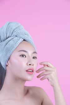 La giovane donna asia con la pelle pulita fresca tocca il proprio fronte, espressioni facciali espressive, cosmetologia e stazione termale.