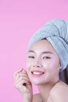 La giovane donna asia con pelle pulita fresca tocca il proprio viso