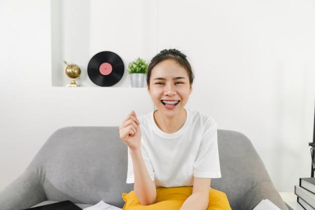 La giovane donna asiatica allegra che si siede sul sofà che guarda e che sorride indossa i ganci con allegro.