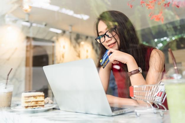 La giovane donna asiatica attraente che utilizza la carta di credito che effettua il pagamento online e le attività bancarie di internet sul computer portatile mentre si siede si rilassa nella caffetteria