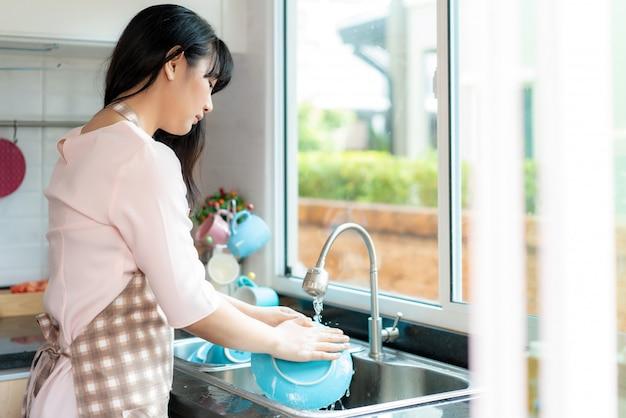 La giovane donna asiatica attraente sta lavando i piatti al lavandino della cucina mentre faceva la pulizia a casa durante il soggiorno a casa usando il tempo libero sulla loro routine di pulizia quotidiana.