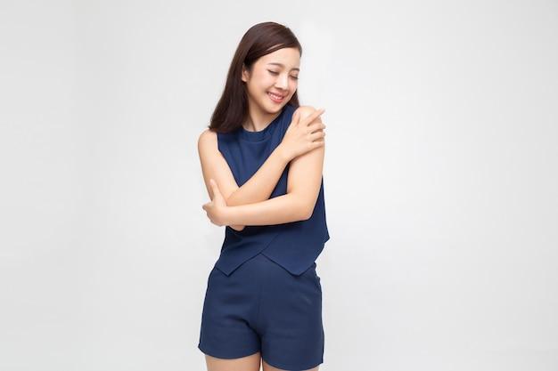La giovane donna asiatica casuale felice che si abbraccia si è isolata su bianco. amare se stessi
