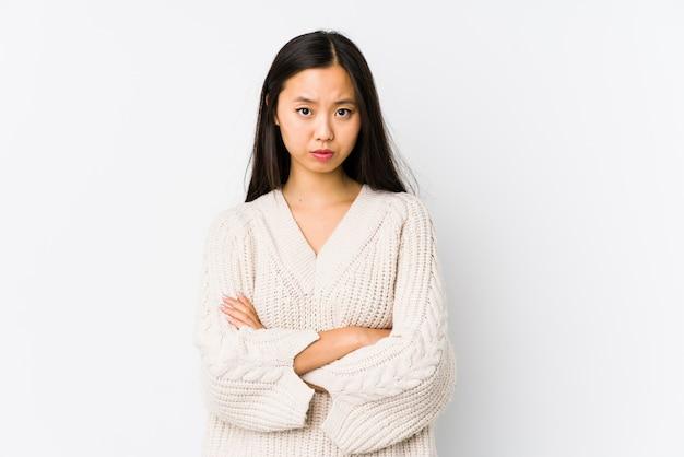 La giovane donna asiatica che aggrotta le sopracciglia nel dispiacere, tiene le braccia conserte