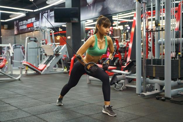 La giovane donna asiatica che fa la corda elastica si esercita alla palestra trasversale di forma fisica.