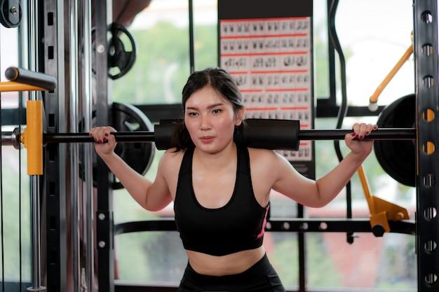 La giovane donna asiatica che gioca l'attrezzatura della palestra all'esercitazione costruisce il suo boday da solo in palestra, misura sportiva per il modello asiatico di stile di vita sano di concetto di ginnastica di pugilato.