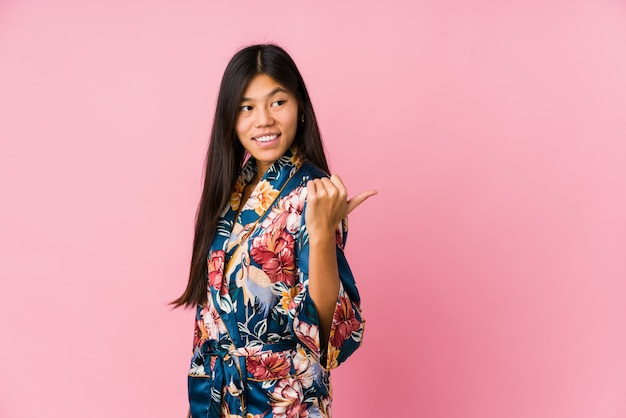 La giovane donna asiatica che indossa un pigiama del kimono indica con il dito del pollice assente, ridente e spensierata.