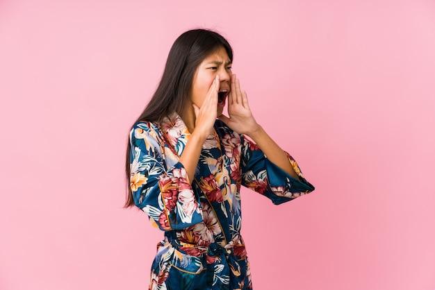 La giovane donna asiatica che indossa un pigiama kimono grida forte, tiene gli occhi aperti e le mani tese