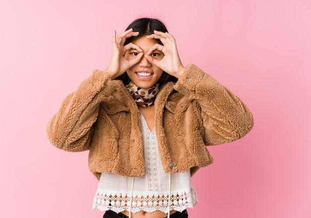 La giovane donna asiatica che mostra bene firma sopra gli occhi