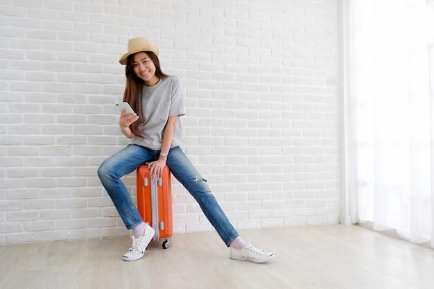 La giovane donna asiatica che si siede sui bagagli che tengono lo smartphone nella stanza bianca, il turista felice dell'adolescente in casuale si siede sui bagagli di viaggio, valigia, bagaglio pronto per il viaggio di vacanza di festa