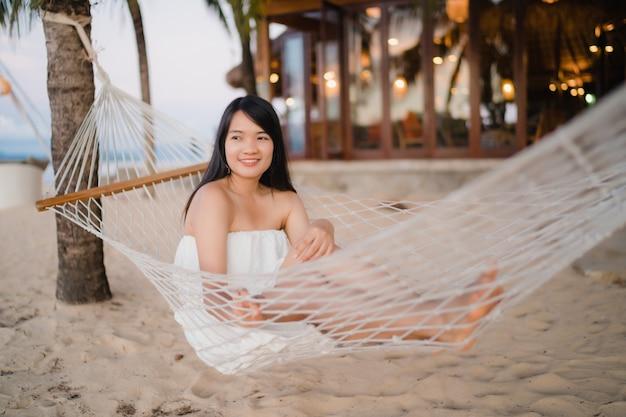 La giovane donna asiatica che si siede sull'amaca si rilassa sulla spiaggia, bella femmina felice si rilassa vicino al mare.