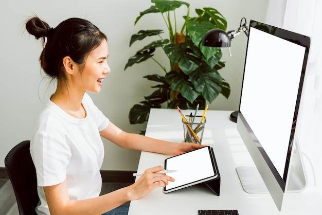 La giovane donna asiatica che si siede sulla sedia e esamina il computer e la compressa digitale commovente con lo schermo in bianco nella casa sulla luce del giorno ha brillato nel pomeriggio.