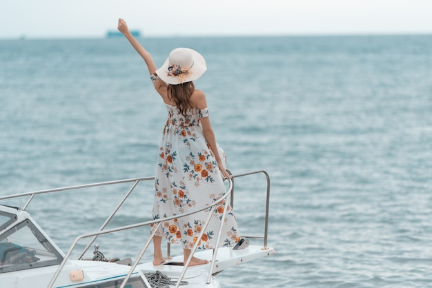 La giovane donna asiatica che sta sulla parte anteriore della piattaforma della barca ha sollevato il braccio su ed esamina un'ampia vista del mare con i capelli lunghi del vento.