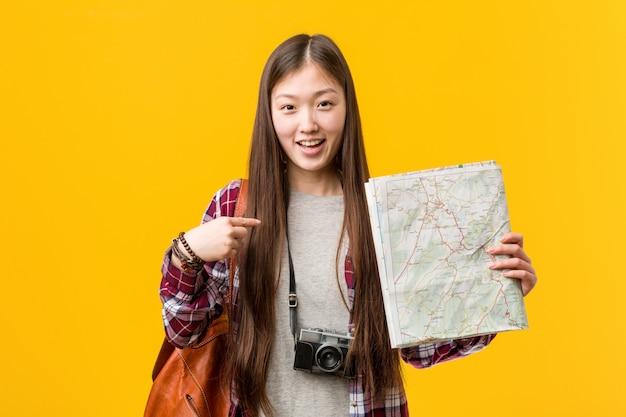 La giovane donna asiatica che tiene una mappa ha sorpreso indicando se stesso, sorridendo ampiamente.